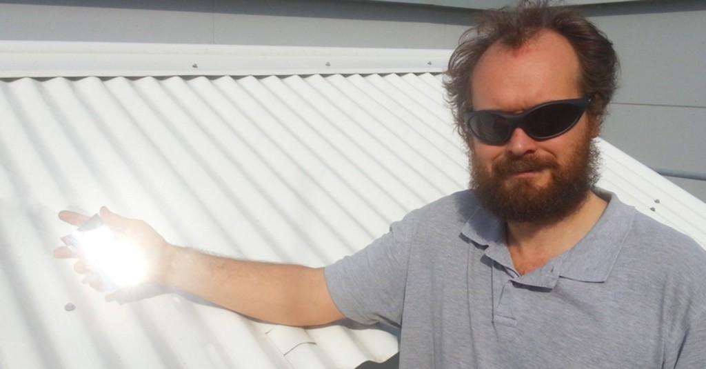 Il dottor Angus Gentle con ina mano un pezzo di materiale speciale sul tetto bianco dell'università utilizzato in fase di test
