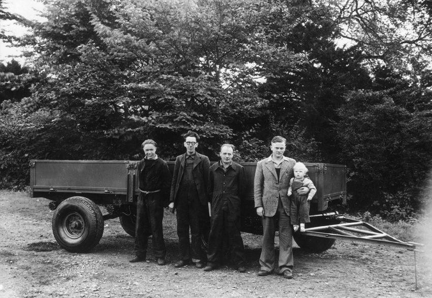 Da sinistra, nel Bill Hirst, Arthur Harrison (dipendente numero uno), Bert Holmes (dipendente numero due) e il fondatore della Jcb, Joseph Cyril Bamford che tiene in braccio un piccolo Lord Bamford
